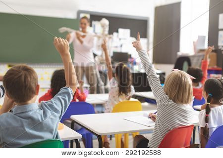 Rear view of kids raising hands while teacher explaining the functioning of human skeleton in classroom at school