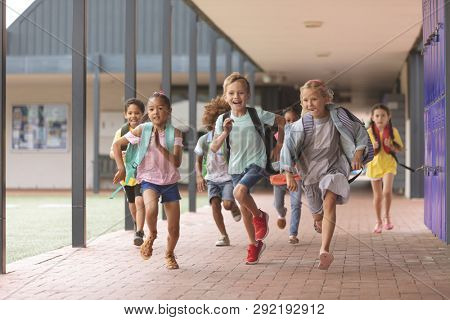 Front view of happy school kids running in corridor at school