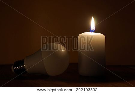 Burning Candle And Lamp On Desktop In Darkness. Broken Electrical Wires Via Storm. Electricity Missi