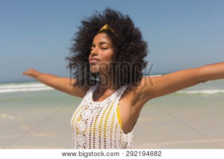 Side view of young African American woman with eyes closed and arms stretched out standing on beach in the sunshine. She is relaxed