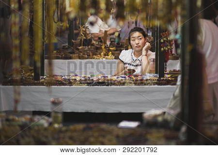 Dunhuang, China - 08 06 2016: A Chinese Craftswoman Selling Souvenirs At Shazhou Market, A Night Mar
