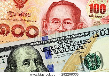 A Close Up Imgae Of A Red One Hundred Thai Baht With An American One Hundred Dollar Bill In Macro