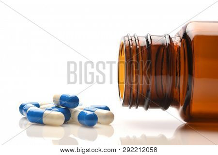 Closeup of a prescription bottle on its side with blue and whiite capsules spilling out.