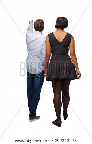 Back view of interracial going couple who points somewhere. walking friendly girl and guy holding hands. Rear view people collection. Isolated over white background. A young couple goes sightseeing poster