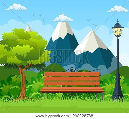 Summer, Spring Day Park. Wooden Bench, Street Lamp In Park , Bushes And Mountains In The Background.