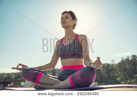 Sporty Young Girl In The Morning On The Pier On Seashore, Practicing Yoga. Woman Do Gymnastics Outdo
