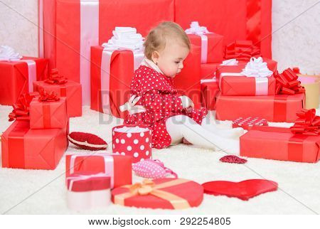 Gifts For Child First Christmas. Little Baby Play Near Pile Of Wrapped Red Gift Boxes. My First Chri