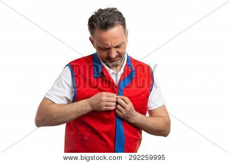 Man working at hypermarket or supermarket buttoning red and blue work attire vest while looking down isolated on white background poster