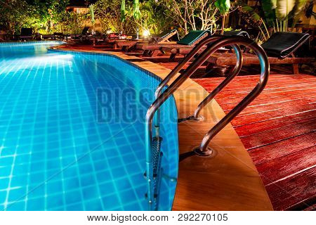 Swimming Pool With Wooden Deck And Stair. Romantic Evening Lighting Setting Near The Pool, Has Lands