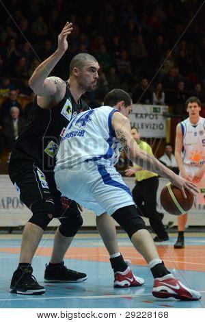 KAPOSVAR, HUNGARY - JANUARY 21: Jozsef Lekli (in white) in action at Hungarian National Championship basketball game with Kaposvar (white) vs. Szolnok (black) on January 21, 2012 in Kaposvar, Hungary.