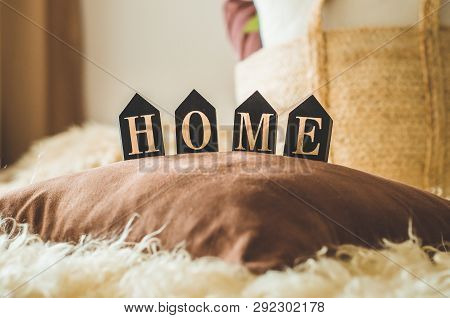 A Lot Of Decorative Cozy Pillows And The Inscription Home. In The Home Interior On The Bed With A Wi