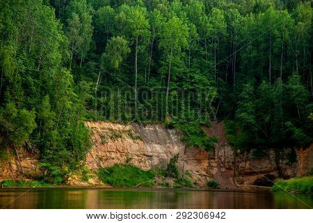 Landscape With Cliff, Flowing River And Green Forest In Latvia. Gauja Is The Longest River In Latvia