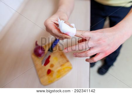 A Woman Cuts Herself With A Knife In The Kitchen