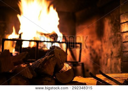Burning Fireplace At Home. Wood Lying Near The Fireplace. Warming Air, Winter Mood