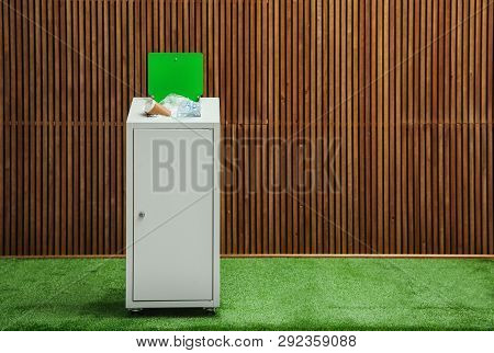 Overfilled Trash Bin Near Wooden Wall Indoors, Space For Text. Recycling Concept