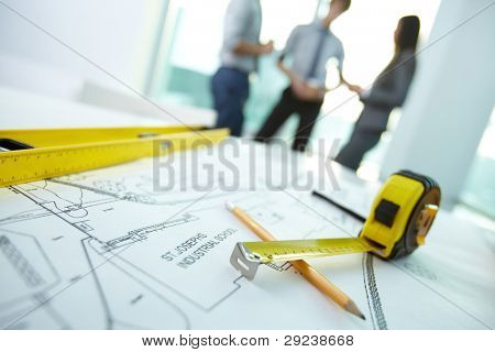 Image of engineering objects on workplace with three architects interacting on background