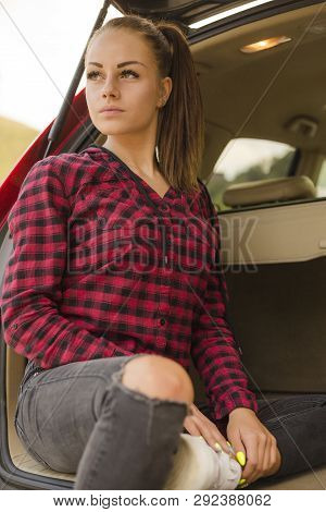 Portrait Of Beautiful Young Woman In Red Shirt And Jeans Posing