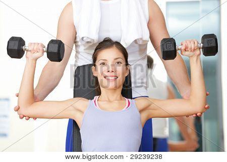 poster of Gym fitness people - woman lifting weights with help from instructor and fitness trainer in gym. Beautiful smiling happy fit female fitness model training shoulders.