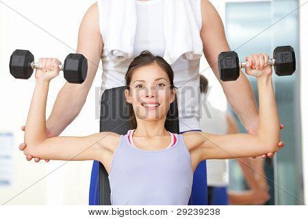 Fitness-Studio Fitness Menschen Frau anhebende Gewichte mit Hilfe von und Fitnesstrainer im Fitnessstudio. BEA