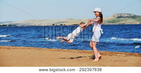 Young Mother In Summer Clothes In Hat Together With Son On Beach. Carefree Playing On Outdoor Sand,
