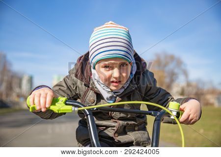 Little Child Boy On Bicycle In Park Outdoor. A Child Is Riding A Childrens Bike