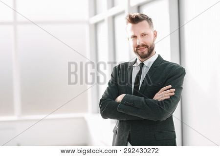 Successful Businessman Standing In A Bright Office