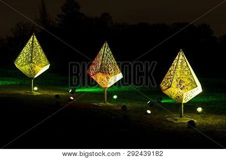 Holiday Fixtures Lit By Colored Floodlights At Night During Holiday Celebration In Park