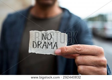 closeup of a young caucasian man on the street, wearing casual clothes, showing a piece of paper with the text no drama written in it