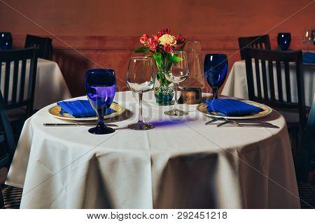 Empty Indoor Restaurant Table. Blue Glasses Set In Restaurant