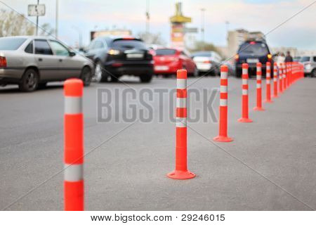 protective barrier made of red striped columns on road, focus on second column