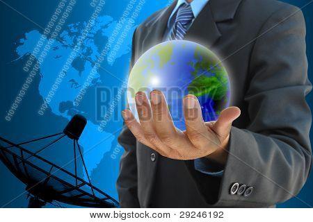businessman hand holding a world and satellite dish antennas background