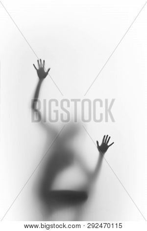 Woman Squatter, And Climb. Human Body Silhouette Can Be Seen Blurred Behind A Diffuse Surface, Only