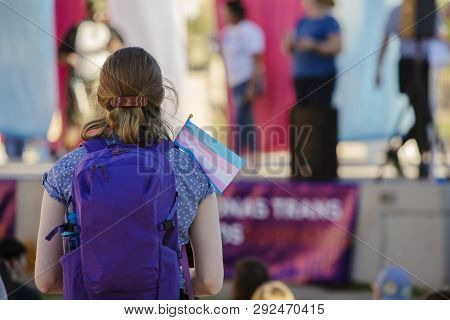 Young Woman With Backpack And Trans Support Flag At A Rally