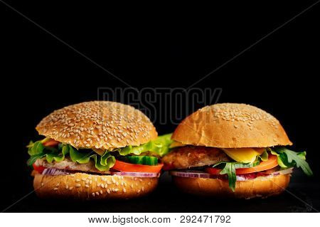 Two Fresh Tasty Sandwiches Isolated On Black Background. Mouth-watering Delicious Burgers. Close-up