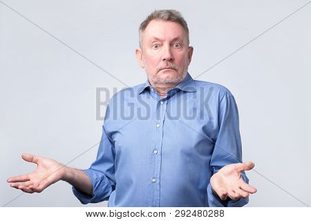 Confused Senior Caucasian Man In Blue Shirt Is Unsure In Studio