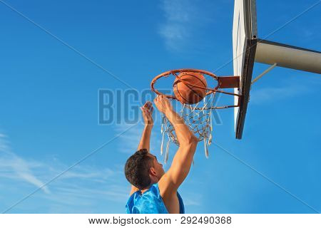 Street Basketball Athlete Performing Slam Dunk On The Court