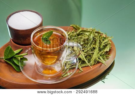 Stevia dry leaves and Stevia sweetener in clayware on mirror background. Stevia have Stevioside (Steviol glycosides) extracted from its leaves. Stevia herb infusion. No sugar added. Stevia healthy concept. Stevia healthy sweetener. Stevia instead sugar.