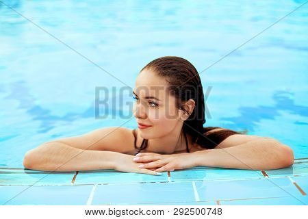 Beautiful Sexy Woman Relaxing In Swimming Pool Water. Girl With Healthy Tanned Skin, Gorgeous Face,