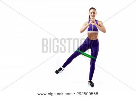 A Ypung Woman Coach In A Sporty Purple  Short Top And Gym Leggings Makes Lunges  By The Feet Forward