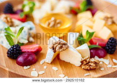 Cheese Plate, Delicious Appetizer To Wine With Fruits, Walnuts, Honey, Served On A Light Wooden Boar