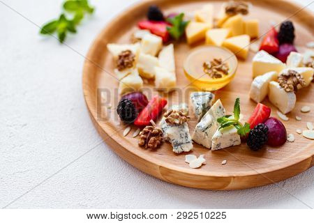 Cheese Plate, Delicious Appetizer To Wine With Fruits, Nuts, Honey, Served On A Light Wooden Board.