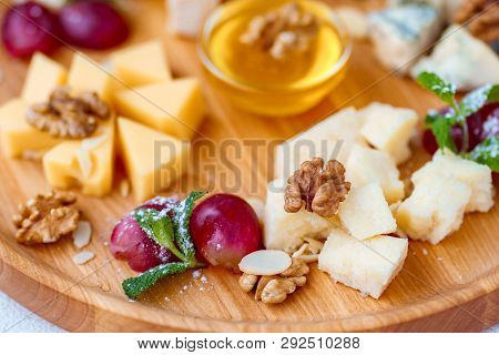 Cheese Plate, Delicious Appetizer To Wine With Grapes, Nuts, Honey, Served On A Light Wooden Board.