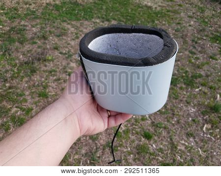 Hand Holding Water Spigot Insulation Cap Or Cover Over Grass
