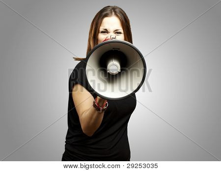 portrait of a young woman shouting with a megaphone over a grey background