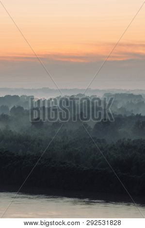 poster of Mystical view on riverbank  of large island with forest under haze at early morning. Eerie mist among layers from tree silhouettes under predawn sky. Morning atmospheric landscape of majestic nature.