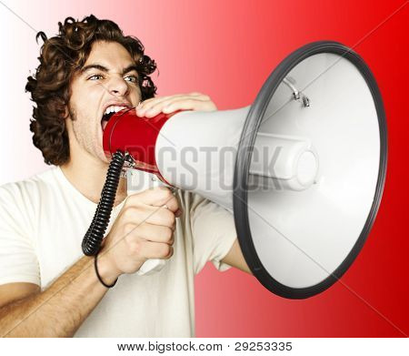 portrait of a young man shouting with a megaphone over a red background