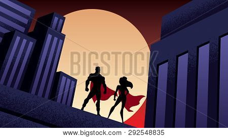 Superhero Couple Watching Over The City From The Roof Of A Tall Building At Night.