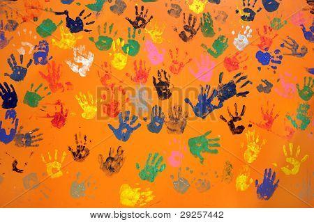 Colored Hand Prints On Orange Wall