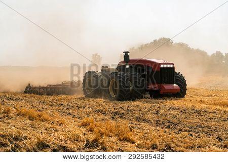A Farmer With Digital Tablet Controls An Autonomous Tractor On A Smart Farm