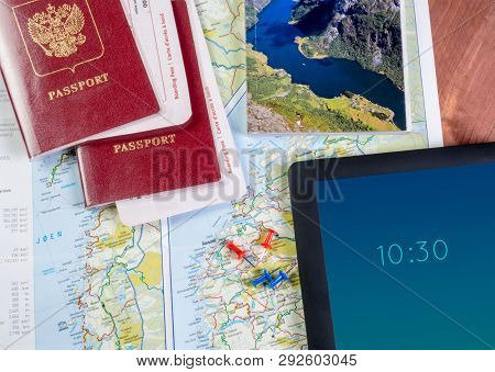 Passports, tourist booklet, compass and pushpins on the map poster